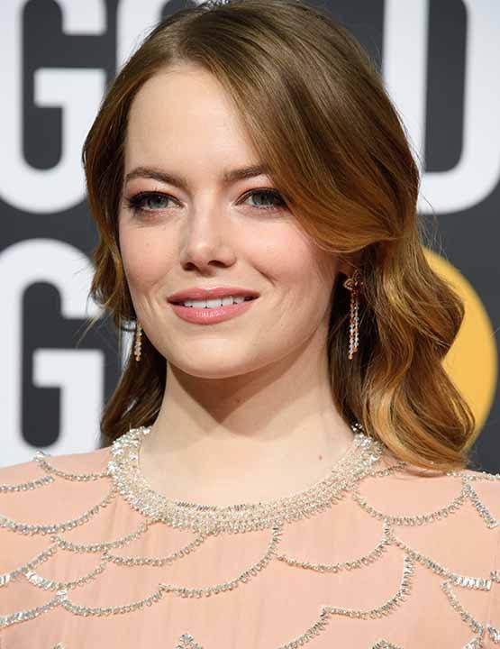 Atriz Emma Stone usa gloss e blush coral nos Golden Globes 2019