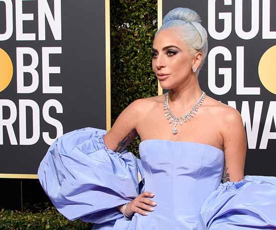 Atriz e cantora Lady Gaga veste vestido azul com um toque de lavanda, by Valentino, no Golden Globe 2019