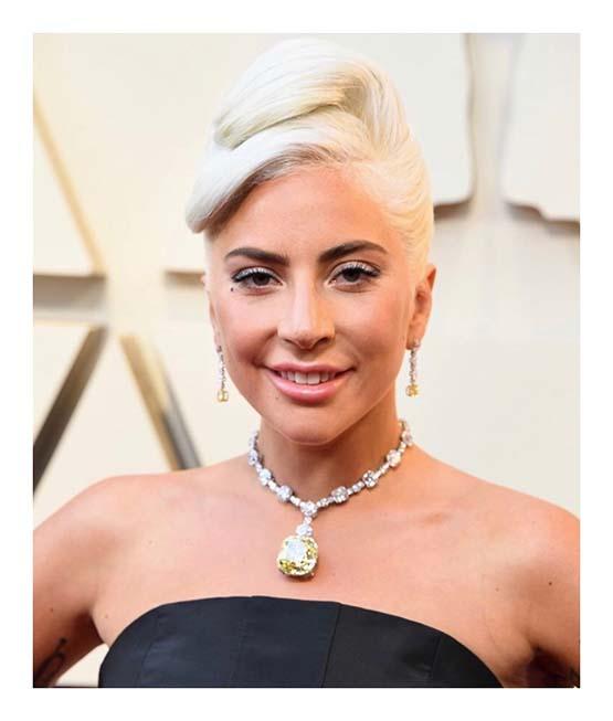 Lady Gaga com coque banana e maquiagem luminosa no Oscar 2019